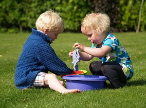 Two blonde kids playing outdoor