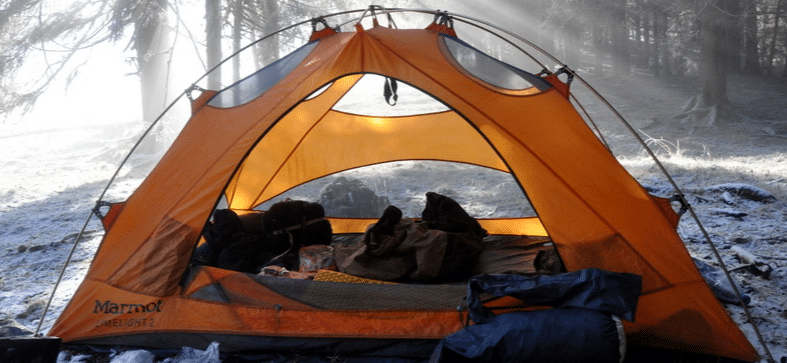 Opened tent with rags and sleeping bags inside